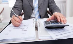 Close-up Of A Businessman Calculating Bills Using Calculator