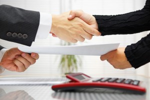 businesswoman and businessman are handshaking and exchanging contract documents