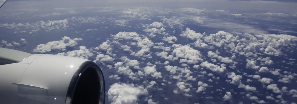 view of ocean and clouds from jet airplane window
