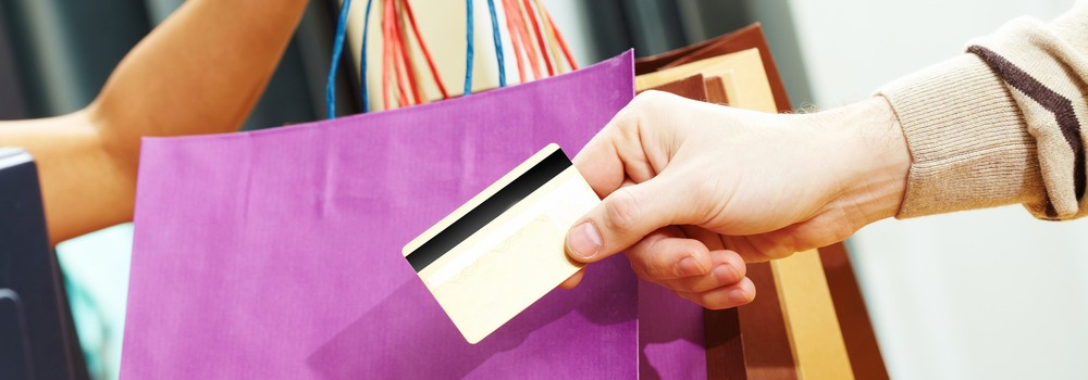 A mans hand passing over credit card to shop assistant after shopping