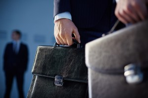 People carrying briefcases on the foreground while their colleague standing on the background