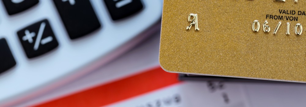 a gold credit card, bank statement and calculator