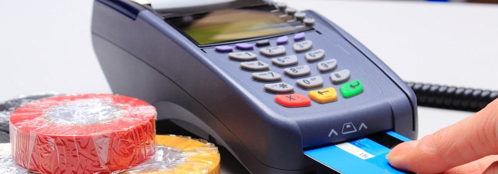 Hand of woman using payment terminal in an electrical shop, paying with credit card