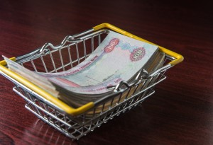 Hundred dirham notes placed in a shopping cart