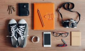 Travel essentials on wooden background