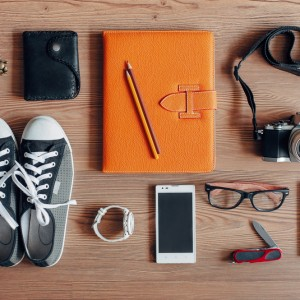 Travel essentials on wooden background