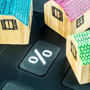 big black calculator with big percentage button and three miniature wooden houses