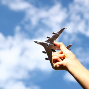 A persons hand holding toy airplane against blue sky with clouds