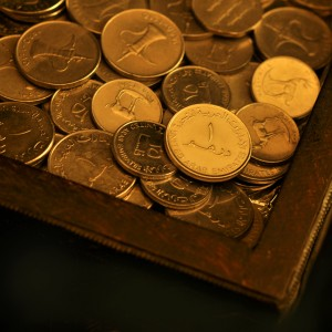 An UAE one Dirham coin in a wooden box
