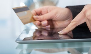 Image of woman using credit card to shop online on digital tablet