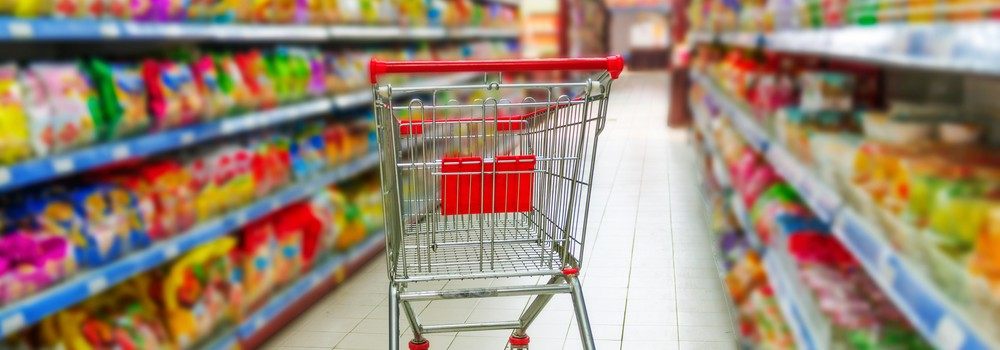 Supermarket with an empty red shopping cart
