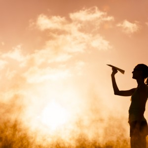 Woman throwing paper plane against a golden sunset
