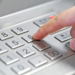 A person entering pin code at the ATM
