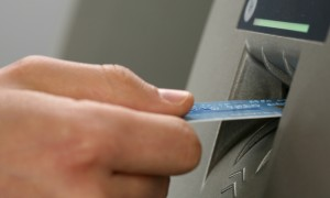 A person inserting a card into an ATM