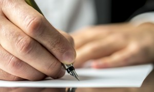 Businessman in a suit signing or writing a document on a sheet of white paper using a nibbed fountain pen