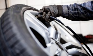 Closeup of mechanic inflating tyre with alloy wheel