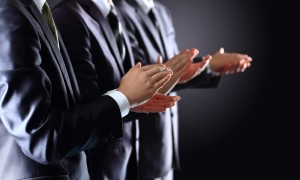 Three people standing hands clapping
