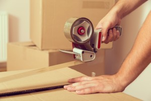 A guy hands holding packing machine and sealing cardboard boxes with duct tape