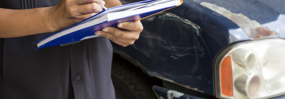 A insurance agent examining car after accident
