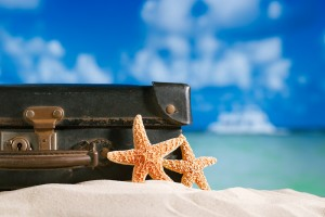 A suitcase on beach with starfish