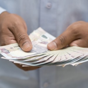 United Arab Emirates Dirhams in mans hand