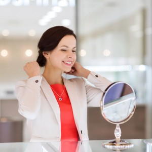 happy woman choosing and trying on pendant at jewelry store