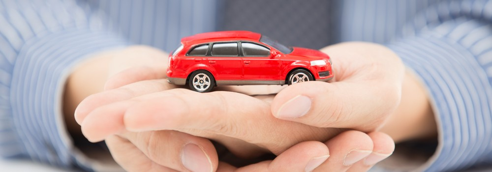 A man holding a toy car in his hand