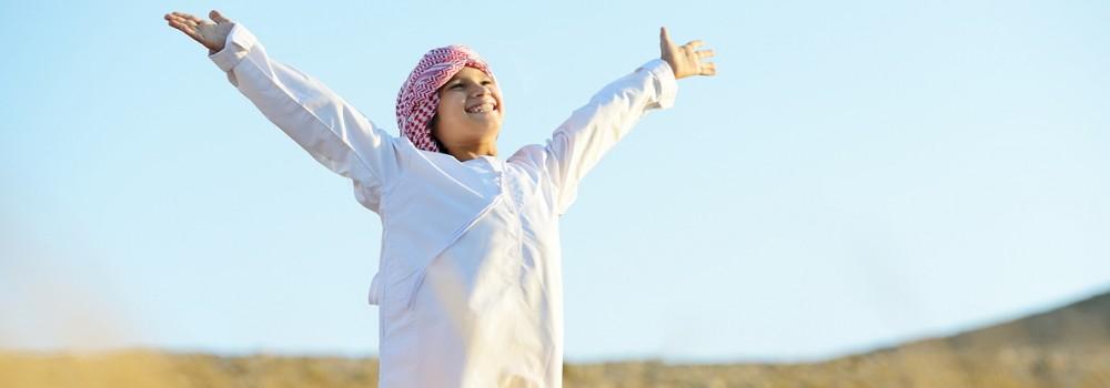 An arab boy standing in a field