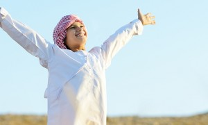 An arab boy standing in a field