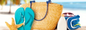 Beach bag, sunblock and slippers on the beach