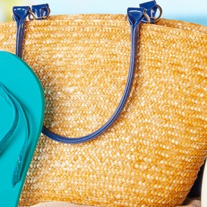 Beach bag, sunblock and slippers on the beach