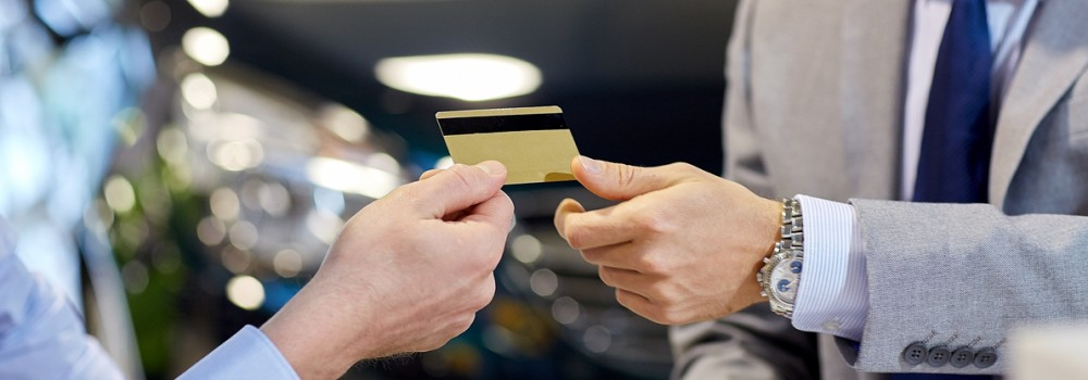 giving credit card to car dealer in auto show or salon (rendered)