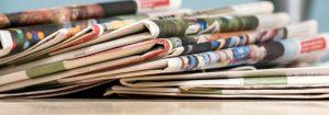 Stack of newspapers - financial headlines rendered