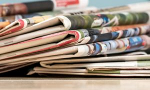 Stack of newspapers - financial headlines rendered
