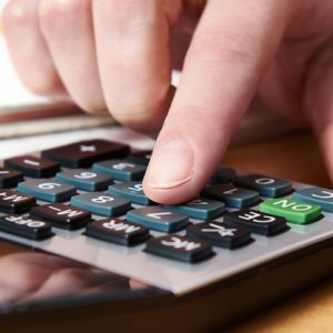 female-hand-using-calculator-cost-of-living-rendered