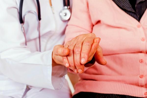 دكتور يمسك بيد عجوز