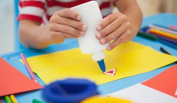 طفل يلصق شكل على ورقة